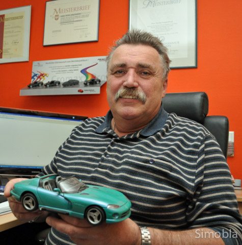 Mit Hilfe von Modellautos demonstriert Peter Langenberg Kunden mögliche Sonderlackierungen. Foto: Michael Sittig