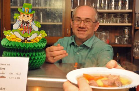 """Eine Portion """"Irish Stew"""" reicht Michael Czich über die Theke im schön dekorierten SKV-Vereinsheim."""