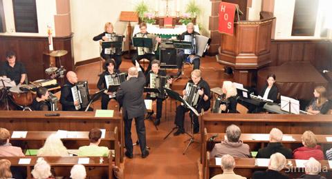 Manfred Klepper dirigierte neun Harmonika-Spieler, zwei Keyboarderinnen und einen Trommler beim Konzert in der evangelischen Kirche.Foto: Michael Sittig
