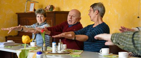 """Bewegungsübungen am Kaffeetisch: Übungsleiterin Gabriele Nagel (rechts) zeigt wie es geht. Links """"Aktiv bis 100"""" – Projektkoordinatorin Helen Rabe-Weber. Foto: Michael Sittig"""