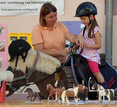 """""""So hält man die Zügel"""", zeigte Sonja Heinisch Mirja, die auf dem Holzpferd Platz genommen hatte."""