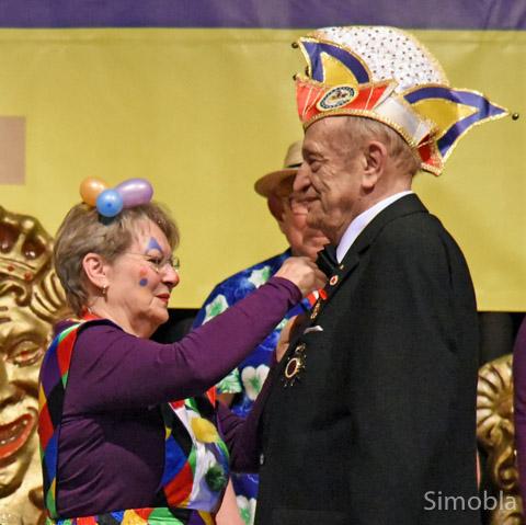 Heidi Derstroff heftet Werner Schmidt die goldene Ehrennadel ans Revers.