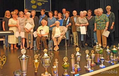 Gründerinnen und langjährige Mitglieder blicken auf die Pokale, die sie im Lauf von 40 Jahren Germania-Frauenchor errungen haben. Fotos: Michael Sittig