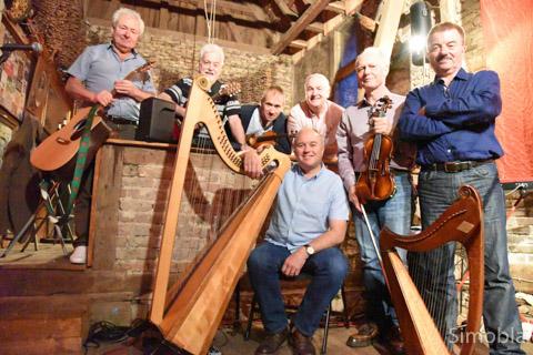 """Mal lebhaft und mitreißend, dann wieder melancholisch und leise zogen die sieben charismatischen Musiker Dave Burns (Gesang, Gitarre, Mandoline, Bodhrán), Iolo Jones (Geige), die Brüder Dafydd und Gwyndaf Roberts (Harfe, Flöte), Geraint Glynne Davies (Gesang, Gitarre), Graham Pritchard (Geige, Mandoline) und Geraint Cynan (Keyboards) das Publikum in ihren Bann. Die walisische Folkgruppe Ar Log gab im Hof von Evelin Wagner und Michael Reisch ein Sonderkonzert für geladene Gäste. Inge Gesiarz, Organisatorin von """"Musik uff de Gass"""" und Tourmanagerin der Band in Deutschland, hatte den Auftritt als kleines Dankeschön für alle möglich gemacht, die bei dem musikalischen Spaziergang im Mai mitgewirkt hatten. simobla/Foto: Michael Sittig"""